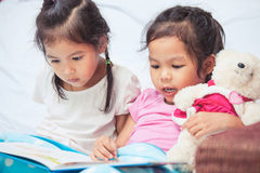 Lovely twin sister two child girls having fun to read a cartoon Royalty Free Stock Images