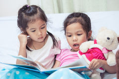 Lovely twin sister two child girls having fun to read a cartoon. Book together in their room Royalty Free Stock Photography