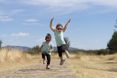 Lovely twins jumping along path in countryside Stock Photo