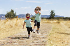 Lovely twins jumping along path in countryside Royalty Free Stock Photo