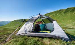 Lovely two people resting in camping at Carpathian mountains. Lovely two people resting in camping at the Carpathian mountains under blue sky at summer day. Near stock photography