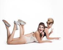 Lovely two women lying on floor in studio on white background Stock Photo