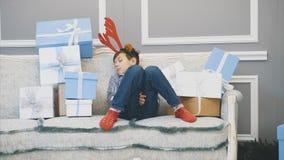 Lovely video of little boy with reindeer headgear, sleeping on the sofa among Christmas presenst.