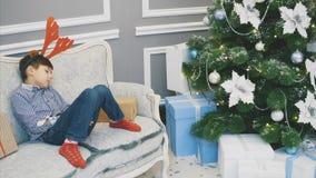Lovely video of little boy with reindeer headgear, sleeping on the sofa among Christmas presenst near fir-tree.