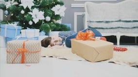 Lovely video of little boy sleeping on white carpet under christmas tree, among Christmas presenst, curling up.