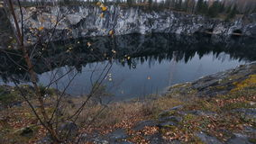 Lovely view of the lake with emerald hill, surrounded by cliffs. Nobody here. Forest reflection in water. Autumn-winter freshness stock video