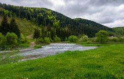 Lovely village outskirts on the river bank. At the foot of the forested mountain. lovely countryside in springtime with overcast sky Royalty Free Stock Photography