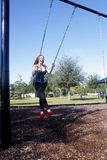 Lovely, Voluptuous Brunette on a Swing (9). A beautiful, young, busty brunette plays in a swing outdoors Royalty Free Stock Image