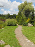Lovely walking path in a park. Walking path made of stones in a beautiful park area with lots of trees and shrubs Stock Photo