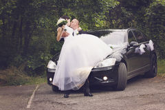 Lovely wedding couple before car Stock Photography