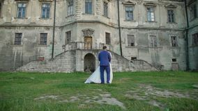 Lovely wedding couple coming to each other and embraces at castle. Slowly stock footage