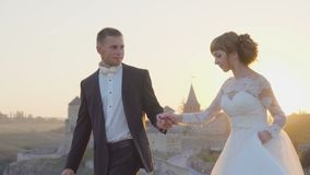Lovely wedding couple kisses each other and embraces near the castle sunset 4k stock video