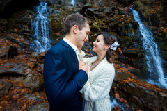 Lovely wedding couple softly holding hands and lovingly look at each other. Waterfall on background.  Royalty Free Stock Image