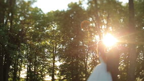 Lovely wedding couple softly kissing in the forest. Beautiful sunset on background. Charming moment