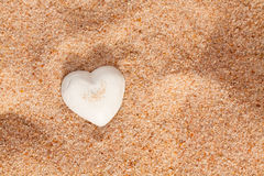 Lovely white shell heart on sand Royalty Free Stock Image