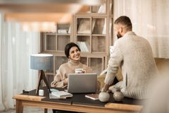Appealing positive couple having conversation together while sitting in office corner. Lovely wife. Appealing positive couple having conversation together while royalty free stock photos
