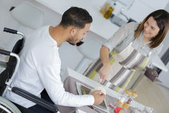 Lovely wife cooking or disabled husband. Lovely wife cooking or her disabled husband Royalty Free Stock Photos