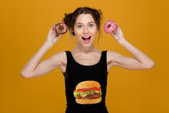 Lovely woman in black top with hamburger print holding donuts Stock Photos