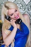 Lovely woman in blue dress  talking on the phone Stock Images