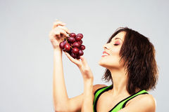Lovely woman with a bunch of grape royalty free stock images
