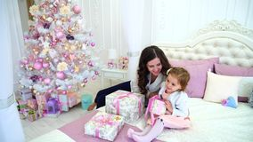 Young Mother And Little Daughter Preparing For New Year Holidays in Spacious Bright Bedroom Sitting on Bed Against. Lovely Woman, Caring Mother Showing Little stock footage