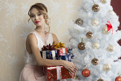 Lovely woman with Christmas presents. Lovely woman with elegant style sitting indoor near decorated tree with some christmas presents on her legs royalty free stock photography