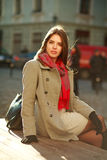 Lovely woman in coat sitting on city street in sunlight Royalty Free Stock Images