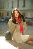 Lovely woman in coat sitting on city street in sunlight Stock Image