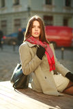 Lovely woman in coat sitting on city street in sunlight Stock Photography