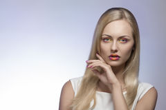 Lovely woman with colorful make-up. Charming blonde woman with spring style, multicolor make-up, long straight hair and white dress Stock Photography