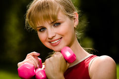 Lovely woman curls dumbbells Stock Photos