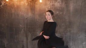 Dancing woman in black dress indoor