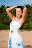 Lovely woman in dress posing against palms Royalty Free Stock Image