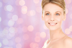 Lovely woman face over pink lights background Royalty Free Stock Image