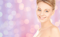 Lovely woman face over pink lights background Stock Image