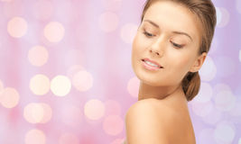 Lovely woman face over pink lights background Stock Photo