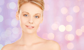 Lovely woman face over pink lights background Royalty Free Stock Photo