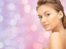 Lovely woman face over pink lights background Royalty Free Stock Photography