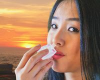 Lovely woman fights the heat by placing an ice cube to her lips stock image