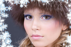 Lovely woman in furry hat over grey Royalty Free Stock Photo