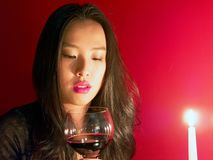 Lovely woman gazes in candle light as she anticipates Valentine`s day. Young Asian girl in the warm illumination of candlelight prepares to take a sip of red stock image