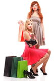 Lovely woman ginger and blonde with shopping bags. Two happy girls ginger and blonde with shopping bags shoes over white Stock Photos