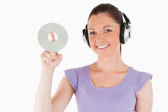 Lovely woman with headphones holding a CD Royalty Free Stock Image