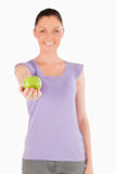 Lovely woman holding an apple while standing Royalty Free Stock Images