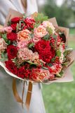 Lovely woman holding a beautiful autumn bouquet. flower arrangement with carnations and red garden roses. Color pink stock photo