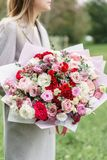 Lovely woman holding a beautiful autumn bouquet. flower arrangement with pink and red color flowers. green lawn on stock photography