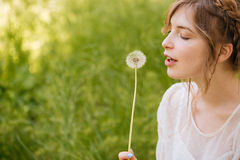 Lovely woman holding and blowing on dandelion outdoors Stock Images