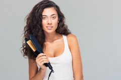 Lovely woman holding hair straightener Royalty Free Stock Photos
