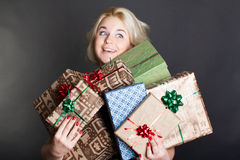 A lovely woman holding a many gift boxes Stock Photos