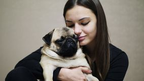 Lovely woman hugging sleepy cute fat pug dog